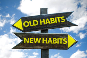 Old Habits - New Habits signpost with sky background